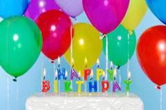Happy Birthday candles on cake with balloons Stock Images