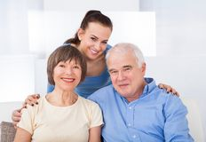 Happy caregiver with senior couple Stock Images