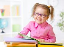 Happy child girl in glasses reading books in room Royalty Free Stock Image