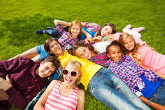 Happy children laying together on green grass Royalty Free Stock Image