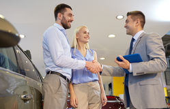 Happy couple with car dealer in auto show or salon Stock Images