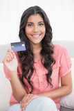 Happy cute brunette sitting on couch showing credit card Stock Images