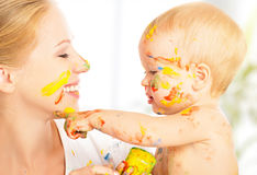 Happy dirty baby draws paints on her face of mother Royalty Free Stock Photos