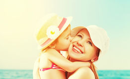 Happy family on beach. baby daughter kissing mother Stock Photography