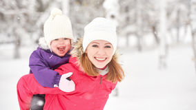 Happy family mother and baby girl daughter playing and laughing in winter snow Stock Photos