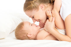 Happy family mother and baby having fun playing, laughing on bed Stock Image