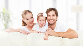 Happy family mother, father, child baby daughter at home on  sofa playing and laughing Royalty Free Stock Image