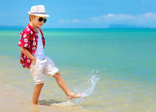 Happy fashionable kid boy walking in surf on tropical beach Stock Images