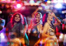 Happy friends dancing in club with holidays lights Stock Images