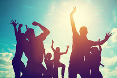 Happy friends, family jumping together having fun. Royalty Free Stock Image