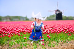 Happy girl in Dutch costume in tulips field with windmill Royalty Free Stock Photos
