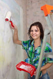 Happy girl paints wall with roller Stock Image