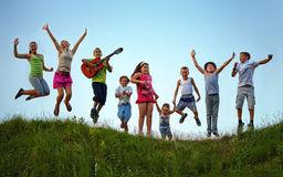 Happy kids jumping on summer field Stock Photos