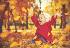 Happy little child, baby girl laughing and playing in autumn Stock Photos