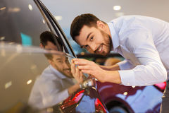Happy man touching car in auto show or salon Stock Photography