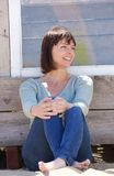Happy middle aged woman in jeans sitting outside Royalty Free Stock Photo