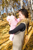 Happy mom and child girl hugging and laughing on nature fall. The concept of cheerful childhood and family. Royalty Free Stock Images