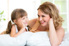 Happy mom and daughter lie on bed Stock Photography