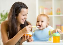 Happy mother spoon feeding her baby child Royalty Free Stock Photography