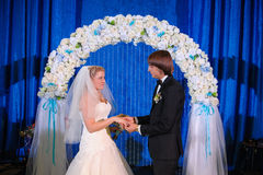 Happy newlywed couple standing in wedding arch Royalty Free Stock Photography