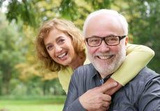 Happy older woman embracing smiling older man Stock Images