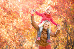 Happy parent and kid walking together outdoor in autumn park Stock Images