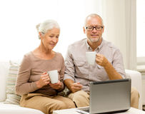 Happy senior couple with laptop and cups at home Royalty Free Stock Photography