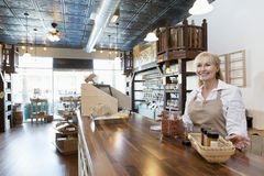 Happy senior female spice merchant standing at counter while looking away in store Stock Photography