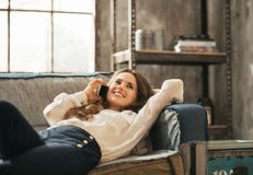 Happy woman laying on sofa and talking cell phone Royalty Free Stock Images