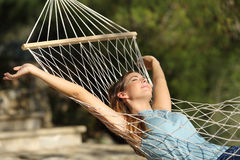 Happy woman relaxing on a hammock on holidays and raising arms Royalty Free Stock Photos