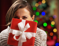Happy young woman holding christmas present box in front of face Stock Photo