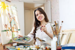 Happy young woman paints   on canvas Stock Images