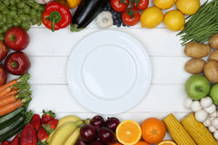 Healthy vegetarian eating vegetables and fruits on empty plate Stock Photo
