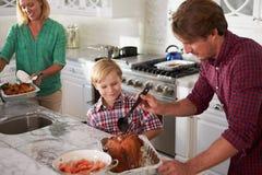 Het Braadstuk Turkije van vaderand son cooking in Keuken samen Royalty-vrije Stock Foto's