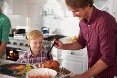 Het Braadstuk Turkije van vaderand son cooking in Keuken samen Stock Fotografie
