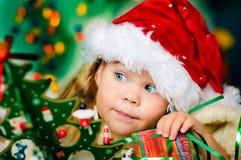 Het gelukkige kleine meisje in de hoed van de Kerstman heeft Kerstmis Stock Foto