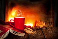 Hete thee of koffie in een rode mok, een boek en een open haard Stock Afbeeldingen