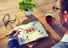 Hipster Writing SEO Concepts on his Note Stock Image