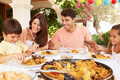 Hispanic Family Enjoying Outdoor Meal At Home Together Stock Image