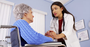 Hispanic woman doctor comforting disabled elderly patient Stock Image