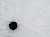 Hockey puck on ice Stock Photos