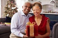 Hoger Paar die Kerstmisgiften thuis ruilen Stock Foto's