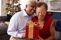 Hoger Paar die Kerstmisgiften thuis ruilen Stock Foto