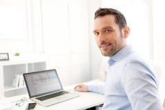 Hombre de negocios joven que trabaja en casa en su ordenador portátil Imagen de archivo libre de regalías