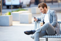 Homem de negócios On Park Bench com café usando o telefone celular Imagens de Stock Royalty Free