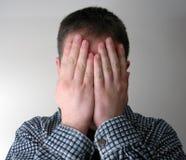 Homme couvrant son visage Photo stock