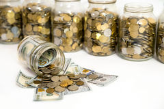 Horizontal shot of coins spilling from coin jar Stock Photography