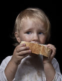 Hungry child eating bread Royalty Free Stock Photo