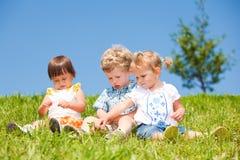 I bambini si siedono su erba Fotografia Stock Libera da Diritti