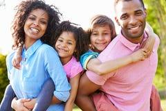 I genitori afroamericani che danno i bambini trasportano sulle spalle i giri Fotografia Stock